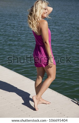 A woman in a pink sun dress is standing on a dock smiling. - stock photo