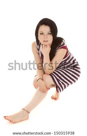 A woman in a purple striped dress sitting. - stock photo