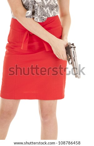 A woman in a red skirt holding a gun. - stock photo