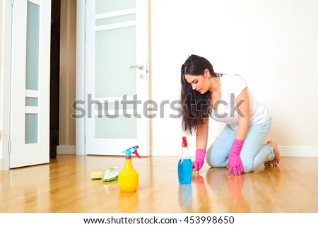 A woman in a room of the house cleaning the floor in rubber gloves. Mom makes wet cleaning of the apartment. Concept of cleanliness and order in the house. - stock photo