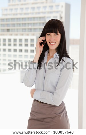 A woman in a sharp business suit at work making a call - stock photo