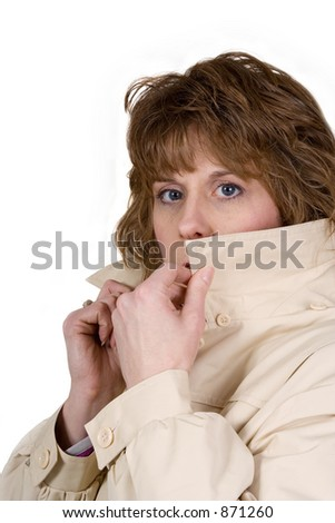 A woman in a trench coat hides behind her collar like a secret agent might do. - stock photo