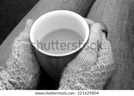 A woman in a warm jumper holding a hot cup of tea or coffee on her lap - monochrome processing - stock photo