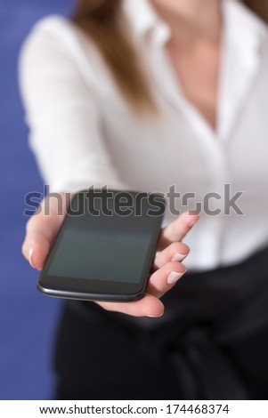 A Woman in a white blouse showing a mobile phone - stock photo