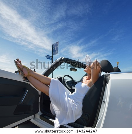 A woman in a white convertible on vacation