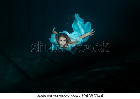 A woman in a white dress as a mermaid swimming under water. - stock photo
