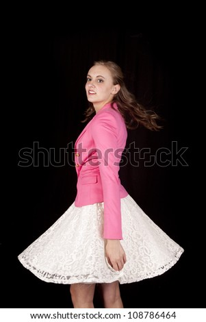 A woman in a white skirt and pink top is spinning. - stock photo