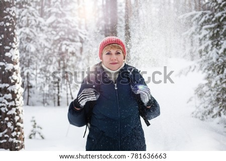 A woman in a winter forest. Beautiful sunny weather and sparkling snow