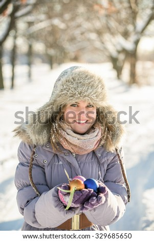 A woman in a winter park. The girl is holding a Christmas balls, decor. A girl wearing a warm jacket and fur hat on hand colored gloves. Girl smiling, portrait. - stock photo