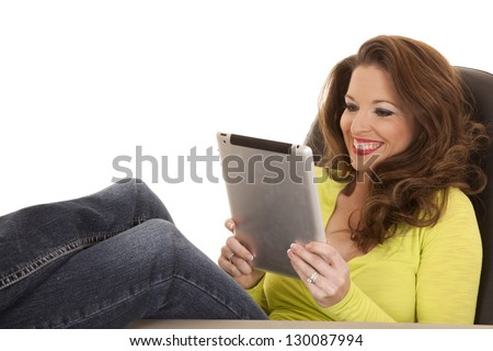 A woman in a yellow shirt has a big smile and working on a tablet.