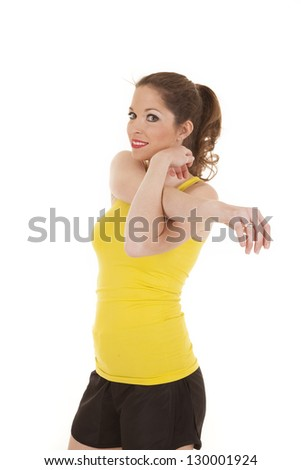 A woman in a yellow tank top is stretching.