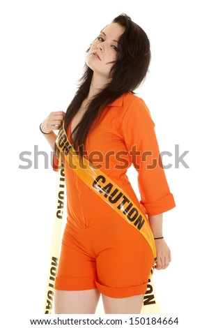 A woman in an orange prisoner jumpsuit with caution tape. - stock photo