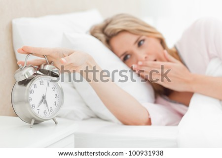 A woman in bed yawning and reaching over to silence the ringing alarm clock beside her bed. - stock photo