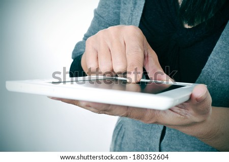a woman in casual wear using a tablet computer - stock photo