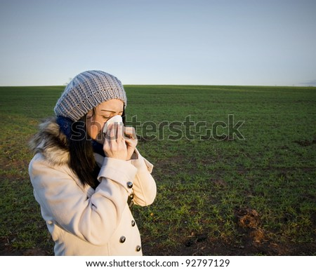A Woman in countryside blowing her nose - stock photo