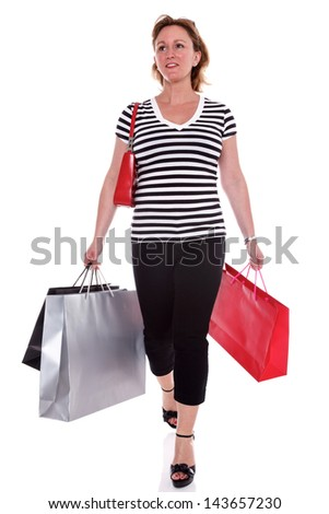 A woman in designer clothing carrying shopping bags, isolated on a white background. - stock photo