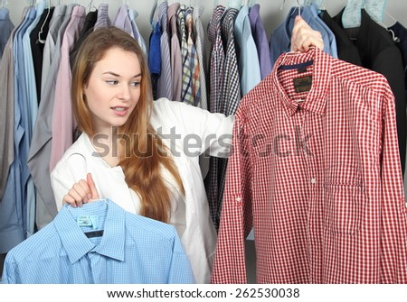 A Woman in Dry cleaning with two dirty shirts - stock photo