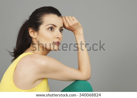 A woman in exercise clothing gazing in thought. - stock photo