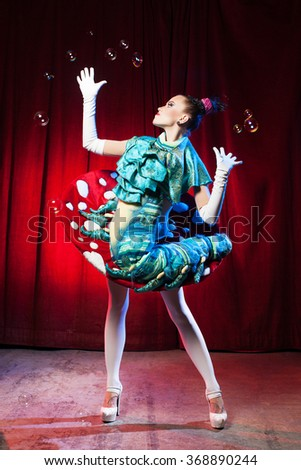 A woman in funny dress plaining with bubble in circus