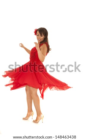 a woman in he flowing red dress spinning and dancing. - stock photo