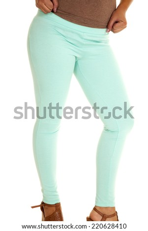 A woman in her baby blue leggings with a brown top and shoes. - stock photo