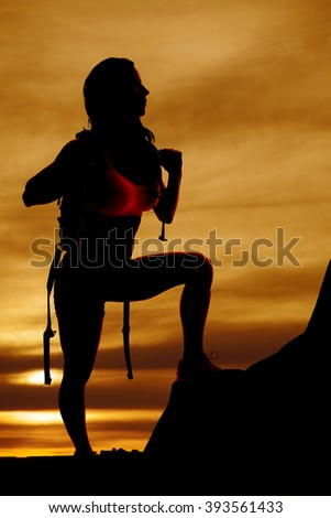 a woman in  her backpack getting ready to climb the side of a mountain