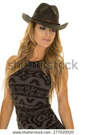 A woman in her black and gray dress, wearing her western hat. - stock photo