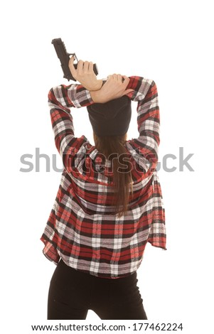 a woman in her black beanie and plaid shirt holding on to a gun. - stock photo