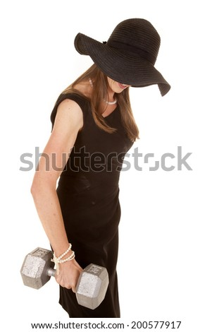 A woman in her black dress and floppy hat, holding on to a weight, trying to fit a workout in.