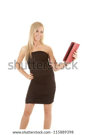 A woman in her black dress looking at her pad in her hand with a smile on her face. - stock photo