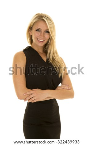 A woman in her black dress with her arms folded and a smile on her face.