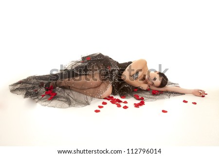 A woman in her black formal with rose petals all around her with a peaceful expression on her face. - stock photo