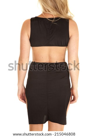 A woman in her black skirt and top, showing off the back of her dress. - stock photo