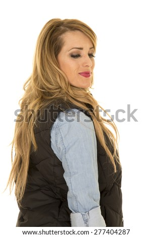 a woman in her black vest and denim looking over her shoulder.