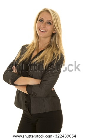 a woman in her business jacket with a smile and her arms folded. - stock photo
