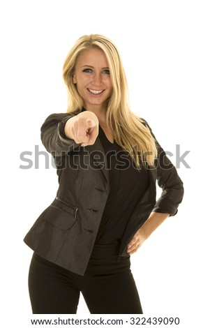 a woman in her business jacket with a smile, pointing her finger at the camera.
