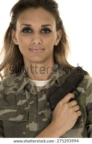 A woman in her camo with her pistol on her shoulder, she has a small smile on her lips. - stock photo