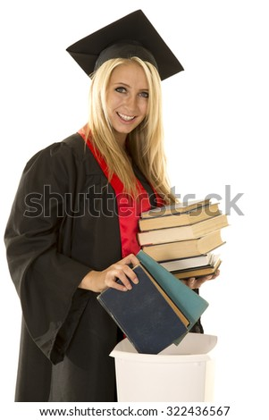 a woman in her cap and gown with a smile, throwing her books away.
