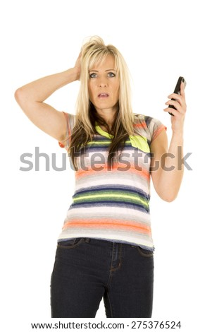 a woman in her colorful shirt with a shocked expression on her face, holding on to her cell phone. - stock photo