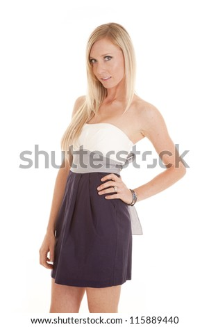 A woman in her dress standing with her hand on her hip and a smile on her lips. - stock photo