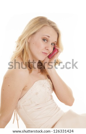 A woman in her fancy dress talking on her cell phone with a smirk on her lips - stock photo