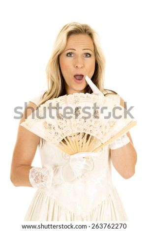 A woman in her fancy dress with a fan, with a shocked expression on her face. - stock photo