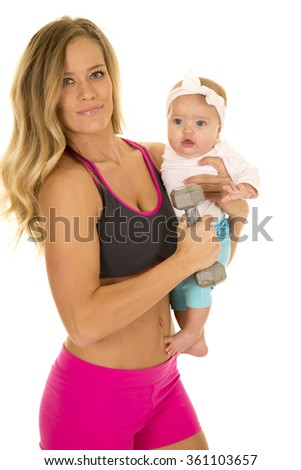 A woman in her fitness clothing holding on to her baby with a weight.