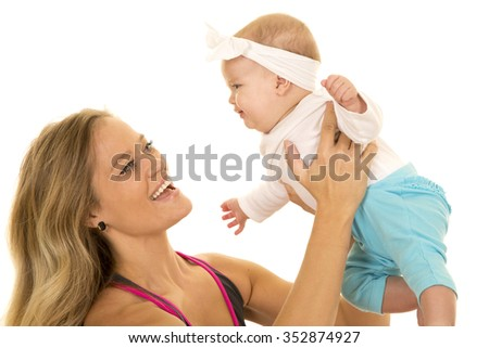 A woman in her fitness clothing holding up her baby girl.