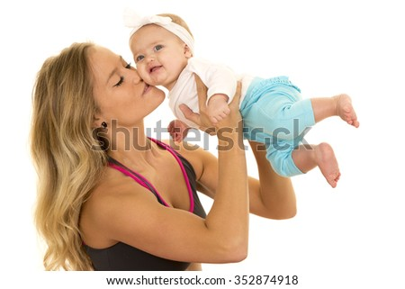 A woman in her fitness clothing kissing her baby girl on the cheek.