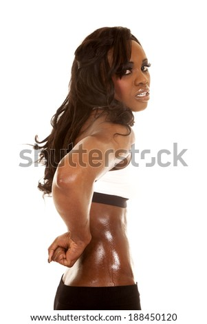 A woman in her fitness clothing sweating with her fist behind her. - stock photo