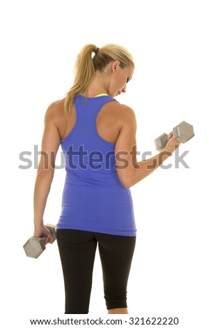 A woman in her fitness clothing with her back to the camera looking down at her arms. - stock photo