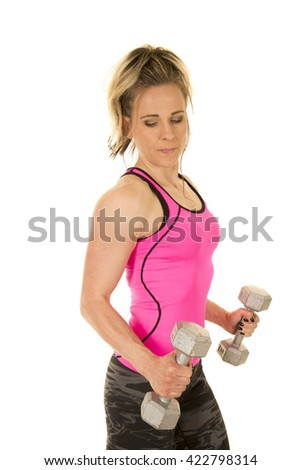 A woman in her fitness clothing working out with weights. - stock photo