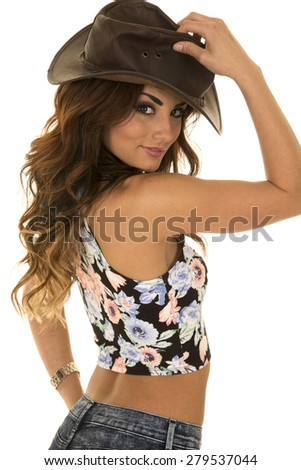 a woman in her flower crop top with her western hat on her head.