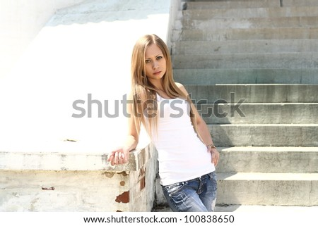 A woman in her forties sits on the staircase for a casual portrait. - stock photo